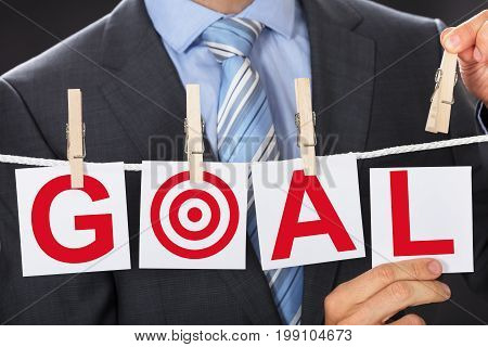 Closeup midsection of businessman pinning GOAL cards on clothesline