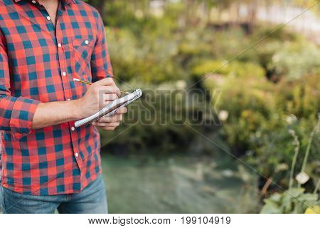 Partial View Of Gardener Making Notes In Notebook While Standing In Garden