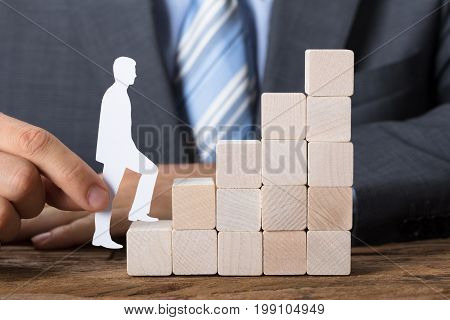 Closeup of businessman moving paper man upstairs made of wooden blocks on table