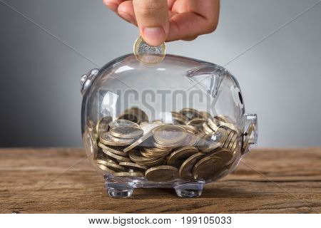 Closeup of hand inserting coin in transparent piggy bank on wooden table