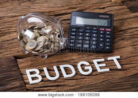 Closeup of transparent piggybank and calculator by budget text on table