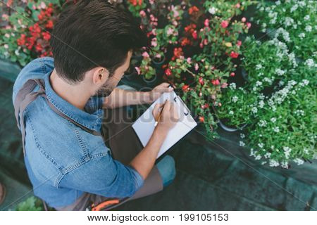 Partial View Of Gardener In Apron Making Notes On Clipboard While Checking Flowers In Greenhouse
