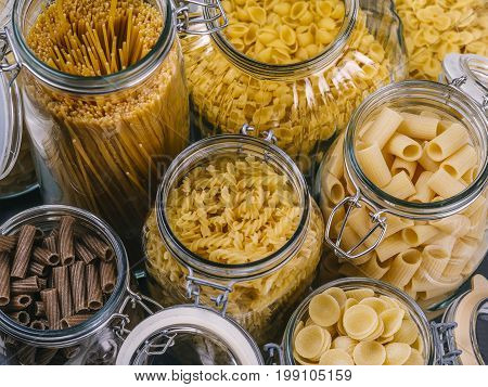Photo of different pasta types in large glass jars.
