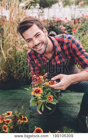 Portrait Of Smiling Gardener Looking At Camera While Holding Flowerpot In Hands In Garden
