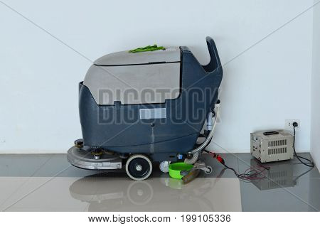 Charging of floor scrubber (cleaning) machine with battery and electricity on white wall