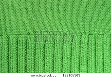 Texture of green woolen knitted fabric background