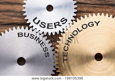 Closeup of users business and technology interlocked cogwheels on wood
