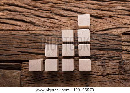 Closeup of increasing bar graph blocks on wooden table