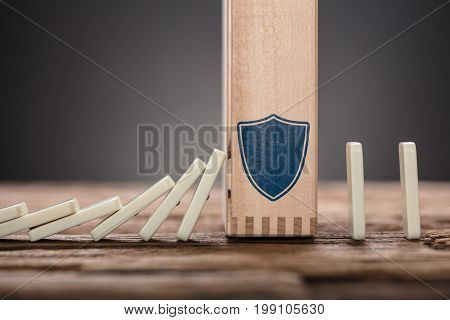 Closeup of wooden block with shield symbol amidst falling and upright domino pieces