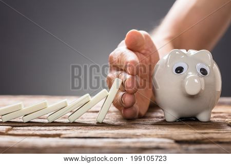 Cropped image of businessman stopping domino pieces falling towards piggy bank on table