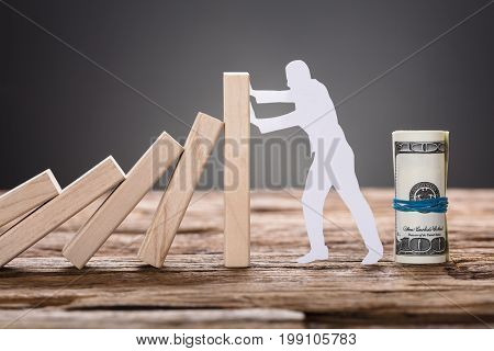 Closeup of paper man stopping wooden domino blocks by rolled up dollars
