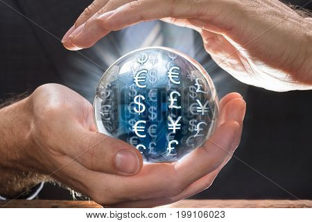 Midsection of businessman covering crystal ball with various currency symbols at table