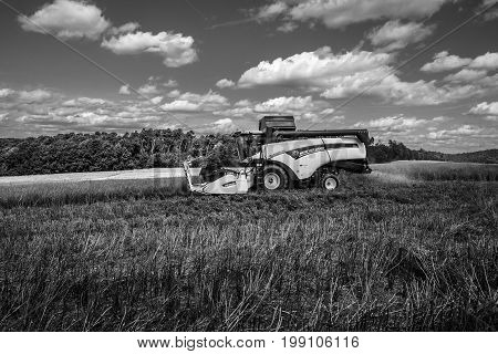 NEUSTADT GERMANY - JULY 30 2017: Harvesting on the fields in the suburbs of the small town of Neustadt (Marburg-Biedenkopf district in Hessen). Harvester on the field. Black and white.