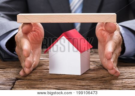 Midsection of businessman covering model home with hands and wooden plank at table