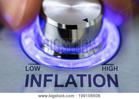 Cropped image of hand turning metallic illuminated knob by inflation text