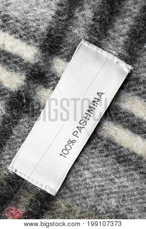 Fabric composition clothes label on plaid wool background