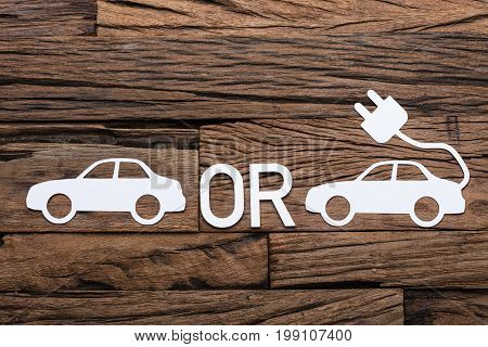 Directly above shot of auto and electric paper cars with OR sign on wooden table
