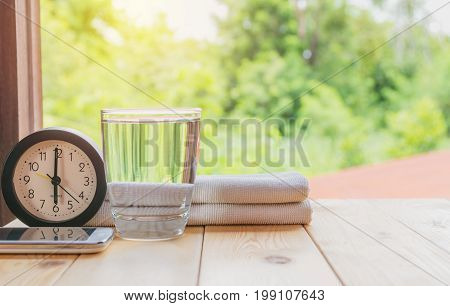 glass of water on a wooden table with clock and handkerchief on nature background.