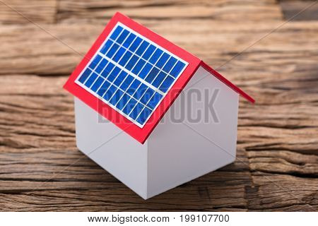 Closeup of solar panel on model home at wooden table