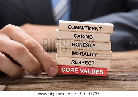Cropped image of businessman holding red core values block under wooden tower at table
