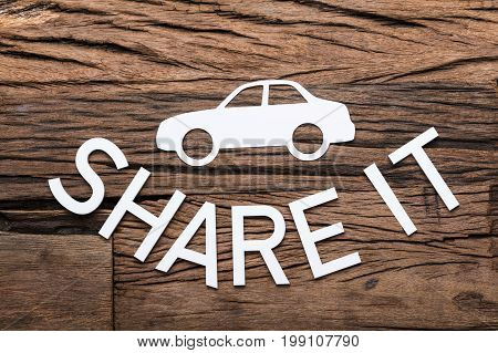 High angle view of paper car and share it text on wooden table