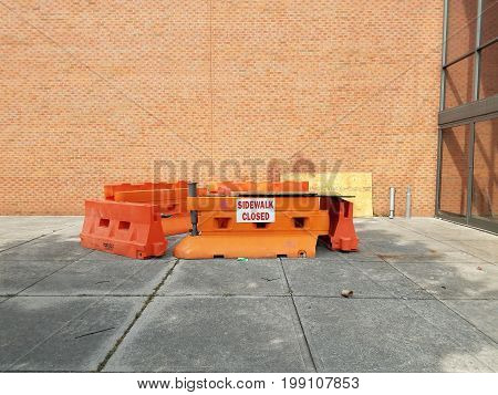 sidewalk closed sign on orange barricades with cement and brick wall