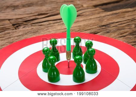 Closeup of green paper team surrounding arrow on dartboard at table