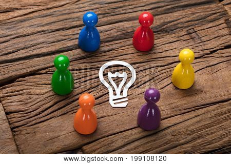 High angle view of multicolored pawn figurines surrounding paper light bulb on wooden table