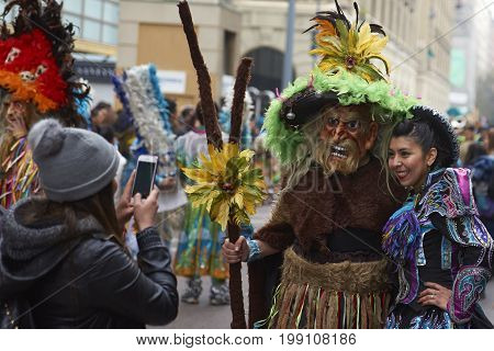 Santiago, Chile - August 5, 2017: Caporales dancer has her photograph taken with a masked Tobas dancer at a parade through the centre of Santiago, Chile to mark Independence Day of Bolivia.