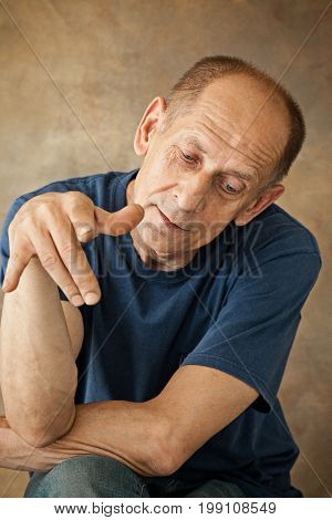 Worried mature man sitting at studio and thinking about something