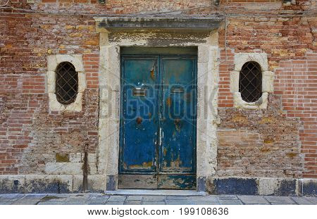 An old wooden door in a derelict building in the Dorsoduro quarter of Venice