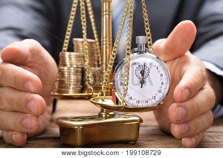 Businessman covering stopwatch and coins on golden weighing scale at wooden table