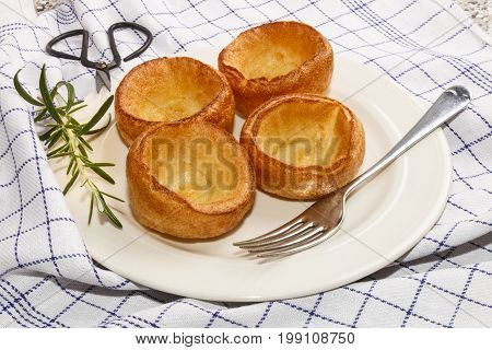 yorkshire pudding with rosemary on a white plate
