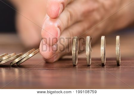 Cropped image of businessman's hand protecting coins from falling while playing domino on table
