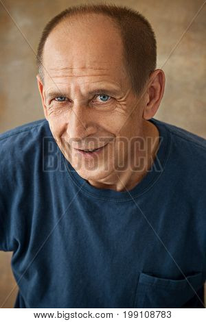 Worried mature man standing at studio and thinking about something