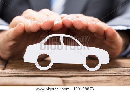 Cropped image of businessman covering paper car on wooden table