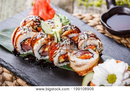 Sushi rolls set with smoked eel red caviar sesame and wasabi on black stone on bamboo mat selective focus. Japanese cuisine