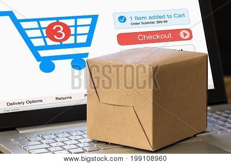 Cardboard box on laptop with pushcart displayed on screen representing online shopping