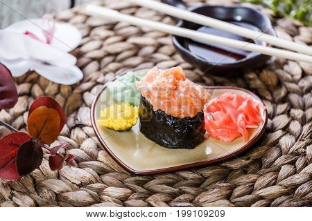 Sushi Gunkan maki with salmon on plate on bamboo mat decorated with flowers. Japanese cuisine. Selective focus