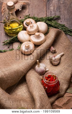 A view from above of white mushrooms, garlic bulbs and bitter pepper on a brown wooden background. A capacity full of sunflowers yellow oil and rosemary on a light fabric. Ingredients for cooking.