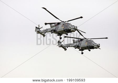 LEEUWARDEN, NETHERLANDS - JUNI 11 2016: Two Royal Navy | AgustaWestland AW159 Wildcat helicopter in action during an air show demonstration at the airbase of Leeuwarden