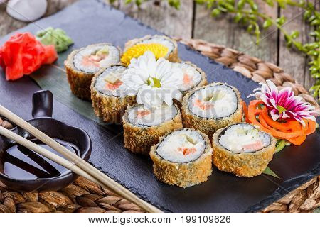 Hot fried Sushi Roll - Maki Sushi with salmon cucumber avocado and cream cheese on black stone on bamboo mat decorated with flowers. Japanese cuisine