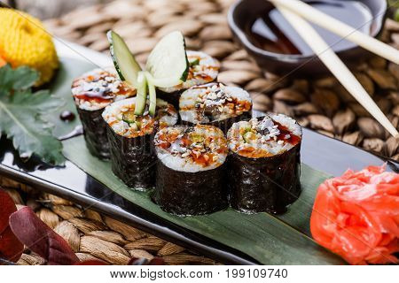 Sushi Roll - Maki Sushi with Smoked Eel cucumber avocado and sesame on black stone on bamboo mat decorated with flowers. Japanese cuisine