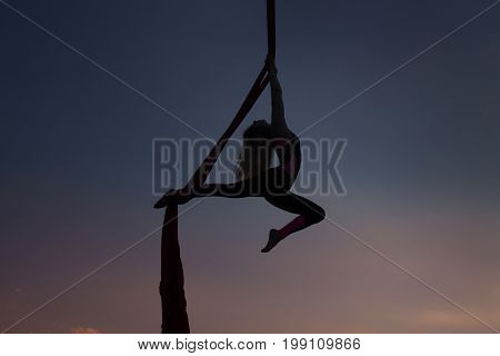 Silhouette of a woman acrobat during a show on canvases in the air.