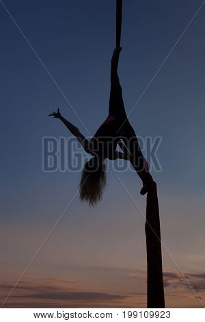 Female acrobat on the poltnakh her silhouette in the sky at sunset.