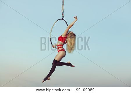 Female acrobat while presenting the show in the air on the hoop.