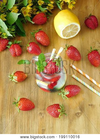 Refreshing soft drink with ice cubes, strawberries and mint surrounded by fresh strawberries on a wooden background. View from above