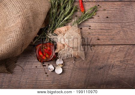 Top view of piquant red chili pepper in a glass jar, green aromatic twigs of rosemary and empty speckled shells of quail eggs on a wooden table on a light wooden background.