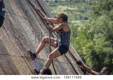 Young woman climbing a rope in extreme sport challenge; physical strength race; concept of courage determination and success
