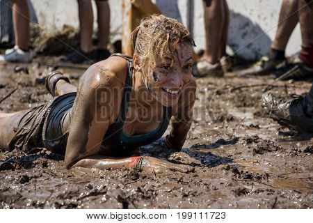 young woman crawling in the mud; participation in extreme sport physical strength challenge